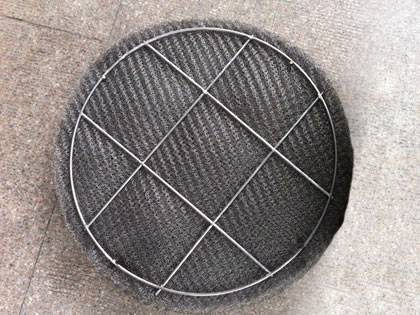 A ginning knitted wire mesh demister pad on the ground.