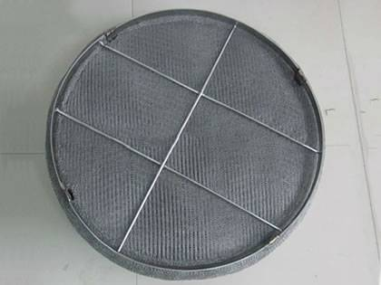 A standard knitted wire mesh demister pad on the ground.