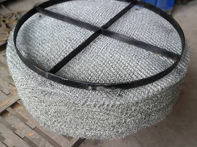 A stainless steel demister pad with carbon steel support grating.